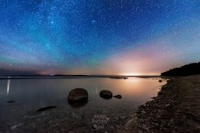 Aurora Borealis activity and air glow color the night sky turquoise over Platte Point on Lake Michigan