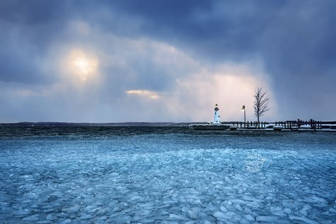 Torch Lake ice shards surround the new Alden Lighthouse under lake effect skies