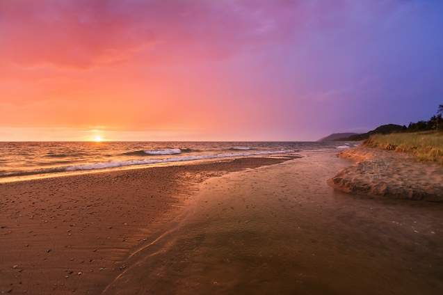 Photo: A glowing sunset sparkles over a creek flowing into Lake Michigan