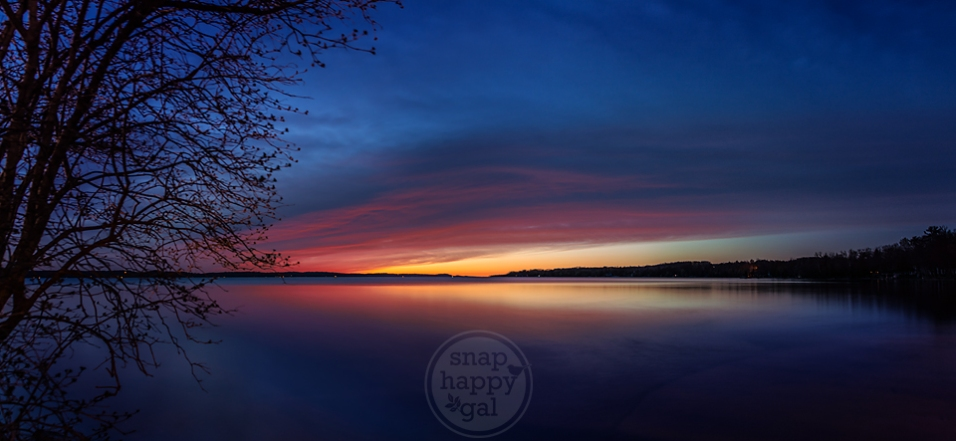 Photo: Red clouds burn above a rainbow sky at sunset over Michigan's Torch Lake