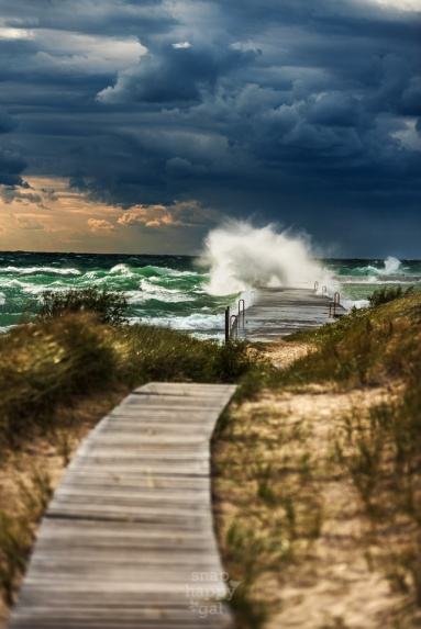 A large Lake Michigan wave crashes into the pier ahead of the boardwalk in Elberta, Michigan
