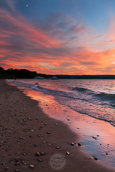 A vibrant sunset reflects off crashing waves at a pebble-strewn beach in Traverse City