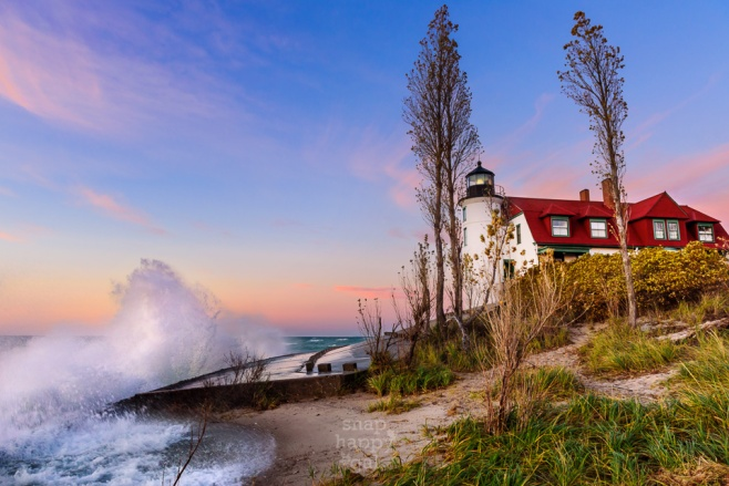 Waves crash on the breakwall at Point Betsie Lighthouse under a cotton candy pink sunset