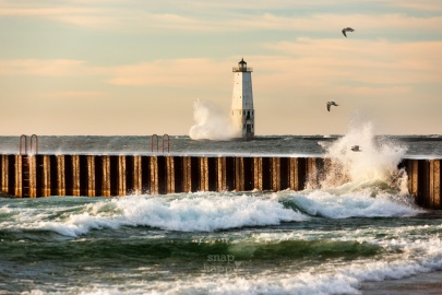 Seagulls and crashing waves adorn the Frankfort Lighthouse in late afternoon sun