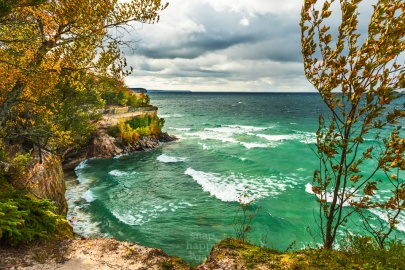 Fall colors highlight some fallen rocks along a Lake Superior Cove at Pictured Rocks