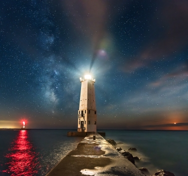 Photo: The lighthouse in Frankfort Michigan lights up a hazy sky under a sky full of glittering stars, the Milky Way, and a setting moon.