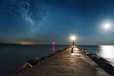 Photo: The lighthouse in Frankfort Michigan lights up its wave-lapped pier under the shimmering Milky Way