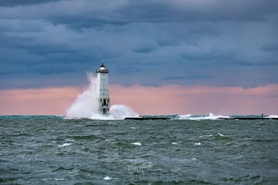 A towering wave bashes the Frankfort Lighthouse under a mellow sunset