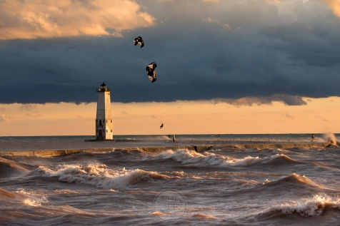 Kite boarders take to the air amid crashing waves at the Frankfort Lighthouse