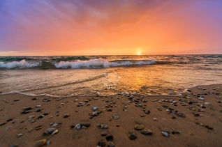 Photo: Gentle waves, pebbles, glowing sunset