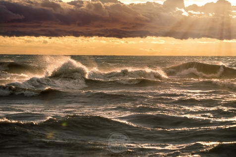 Light rays shine down on toppling waves during a summer gale on Lake Michigan