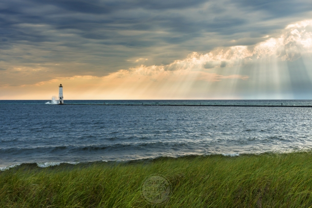Light rays pour down over Lake Michigan at the Frankfort Lighthouse
