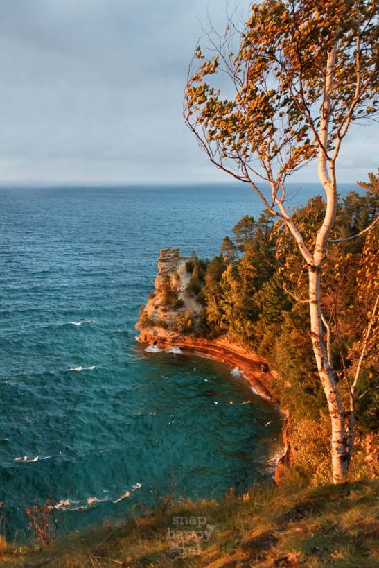 Golden sunset light paints the tree and rock formation at Miners Castle in the Pictured Rocks National Lakeshore
