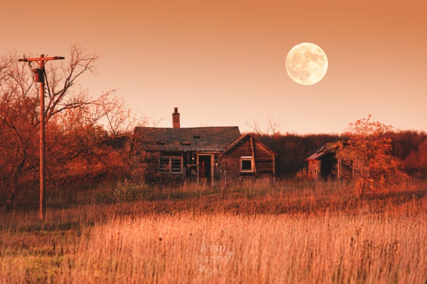 A full moon looms over a decaying Leelanau homestead in red sunset light