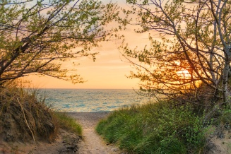 Photo: A peachy sunset beckons down a sandy path to blue Lake Michigan waters