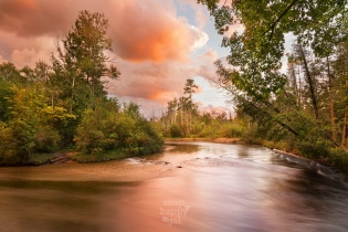 Pink storm light reflects off the swift waters of the Boardman River
