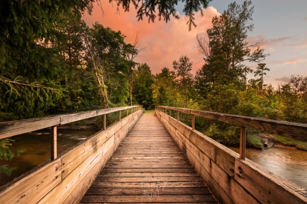 A footbridge over the Boardman River leads to a pink sunset sky