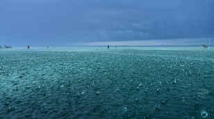 Photo: Large raindrops splash in Lake Michigan's blue waters after a summer storm's arrival
