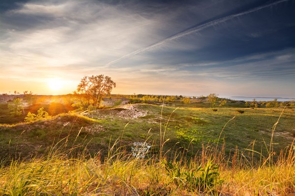 An orange and blue sunset viewed from a plateau within the Sleeping Bear Dunes