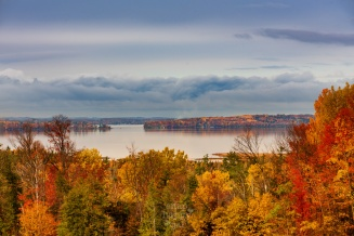Brilliant fall colors surround a still Lake Skegemog on a moody autumn day