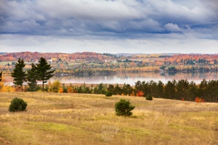 Warm fall colors in the hillsides around Lake Skegemog are doubled in reflection under moody skies