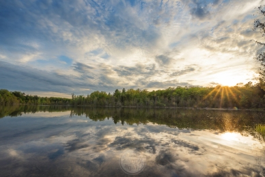 A golden sunset reflects in Fern Lake at the Timbers Recreation Area outside Traverse City