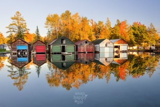 A collection of colorful boathouses form perfect reflections in the Torch River near Alden, Michigan
