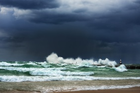 Violent Lake Michigan waves crash in a spray of white against a dark, stormy sky