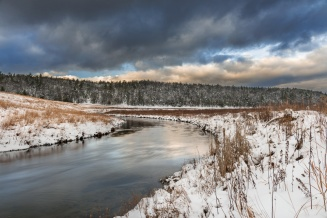 Dramatic lake effect skies hang over a snow-surrounded Boardman River