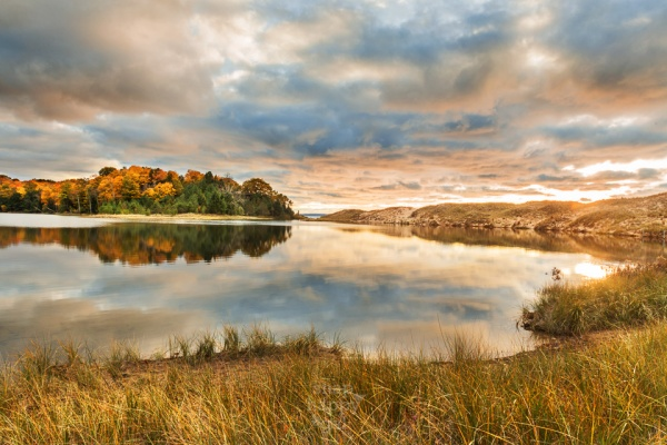 A warm, textured sunset reflects in the smooth surface of North Bar Lake in the Sleeping Bear Dunes