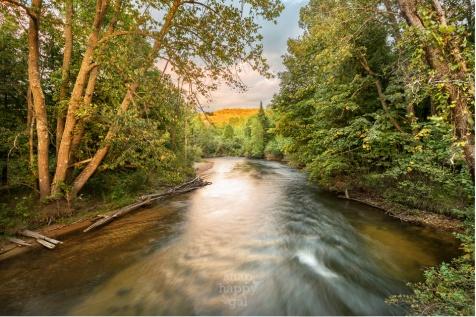 The last rays of light flush the hillside golden over the Boardman River