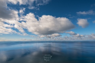 Lake Michigan's calm surface reflects beautiful blue skies and white, puffy clouds