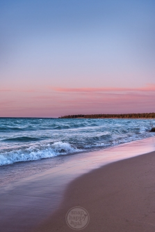 A pink sunset infuses the beach with color at Wilderness State Park in northern Michigan