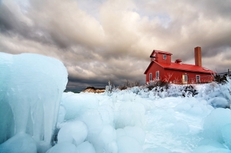 Photo: Blue ice formations below red fog signal building