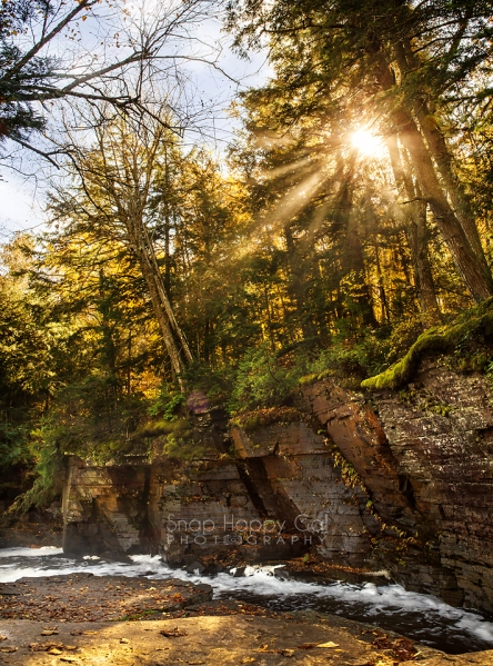 Photo: Fall sun shines through the trees beyond Canyon Falls on the Sturgeon River