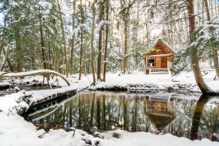 Photo: Snowy log cabin above still creek
