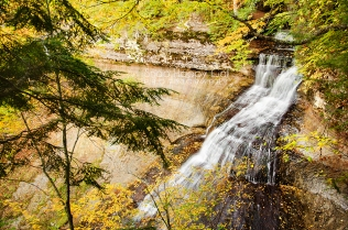 Photo: Chapel Falls waterfall cascades over smooth rocks, fallen leaves nearby