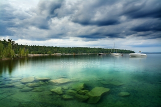 Photo: storm clouds over clear turquose water
