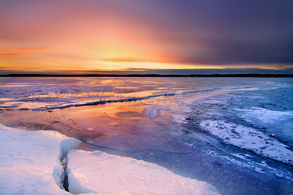 Photo: Glowing sunset reflects off a frozen Torch Lake