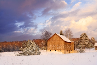 Photo: Snow covered barn catches the warm light of sunset