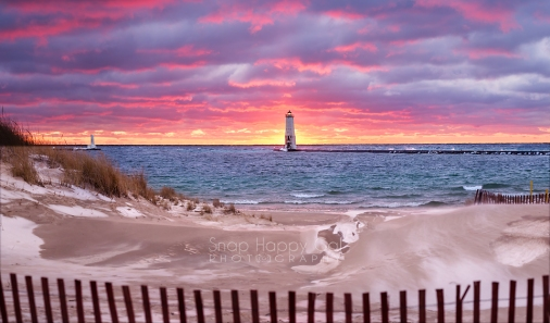 Photo: red sunset over the Frankfort lighthouse, beach and fence