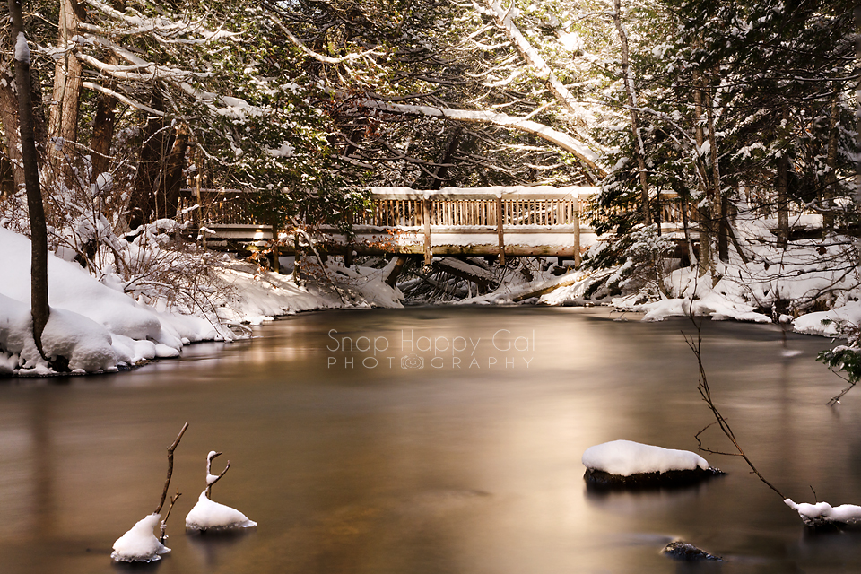 Photo: snowy footbridge over smooth water