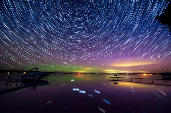 Photo: Stars circle above an aurora filled night sky overlooking Alden, Michigan
