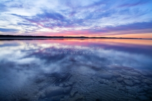 Photo: Crystal clear waters of Torch Lake reflect a red sunset