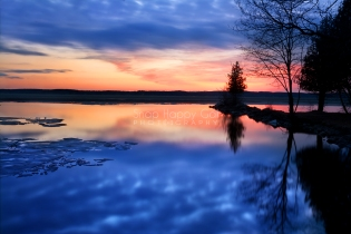 Photo: sunset and silhouettes reflect in still Torch Lake waters