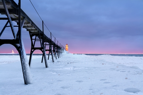 Photo: pink and purple sunrise over the pier and frozen Manistee Lighthouse