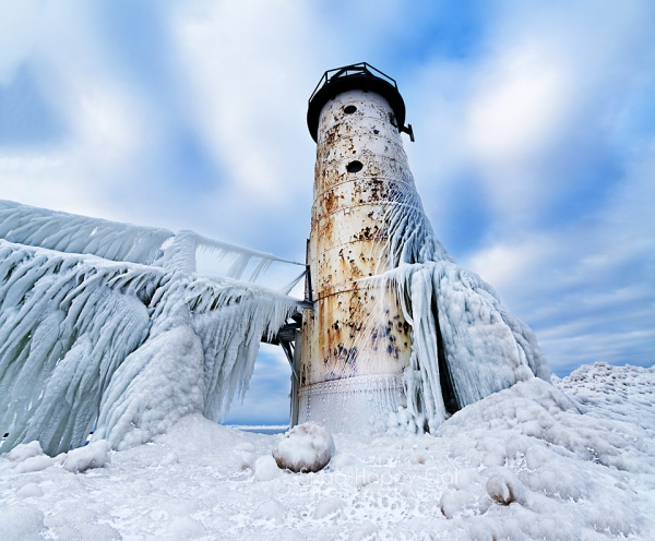 Photo: Winter's gnarly ice clings to the rust-flecked Manistee Lighthouse in Michigan
