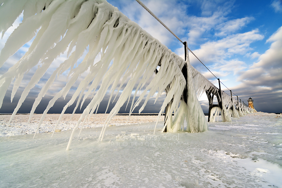Photo: Dark skies split dramatically over the ice-covered pier at the Manistee Lighthouse