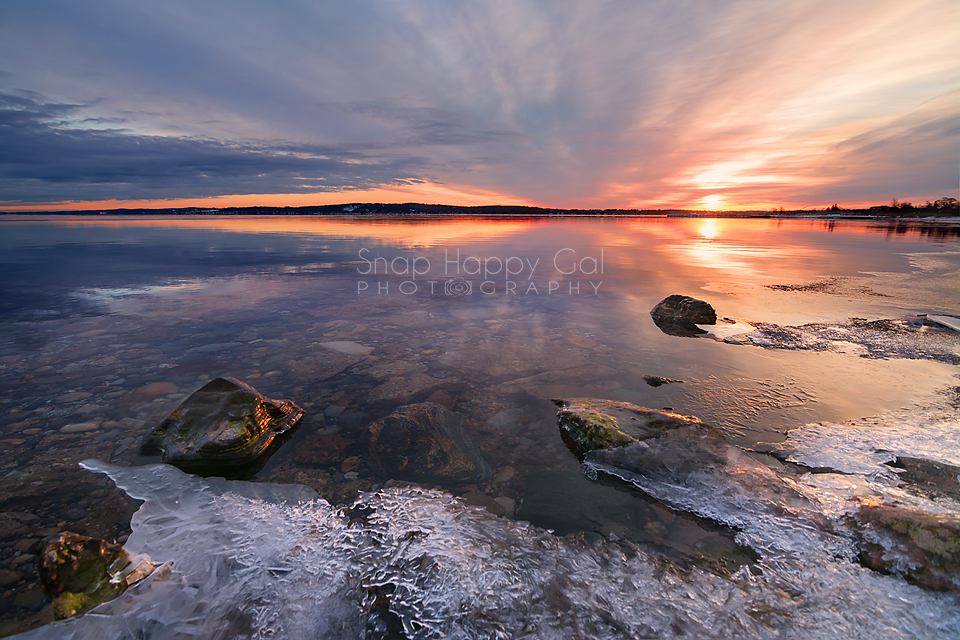 photo: A vibrant sunrise plays on the horizon over the still waters of an icy Lake Michigan bay in Traverse City