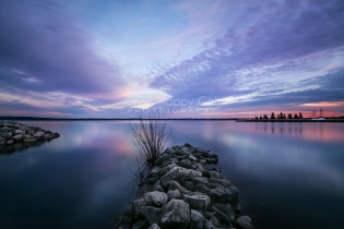 Photo: Rocky breakwalls jut into the smooth waters of West Traverse Bay at sunset